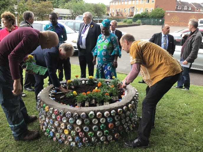 Bishop John of Warwick planting a marigold at The Day of the African Child, while other VIPs chat to OWL members.